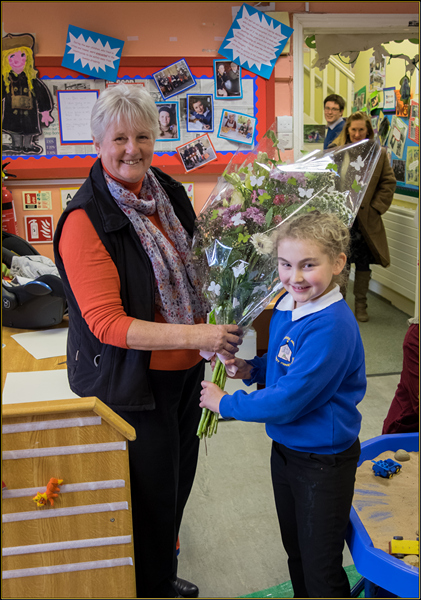 Olivia Dring , a pupil at the school, presents a bouquet.